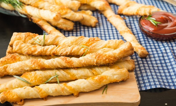 Golden-brown parmesan breadsticks with a bite of pepper