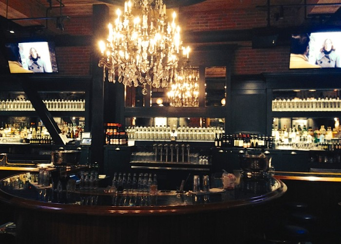 The Distillery Bar + Kitchen has a moody interior dining room lit by chandeliers .