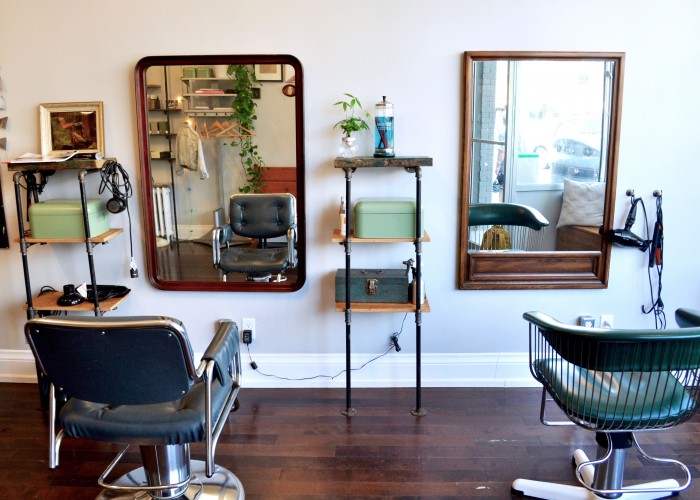 Lebel & Crowe's styling area is accented by vintage salon chairs, each facing antique mirrors and rustic shelving where the stylists stock their minimal tools.