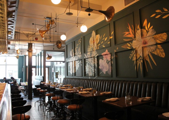 Flowers adorn the walls at Miss Thing's, and there are golden horns for light fixtures.